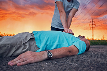 Man performing CPR on man lying on ground with storm and sunset in sky