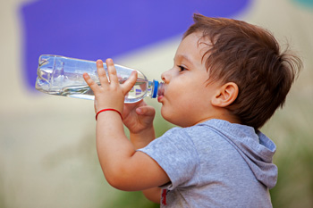 Little boy drinking bottle of water