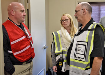 People stand in hallway facing each other while wearing safety vests