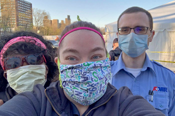 Three people wearing masks with cityscape in background