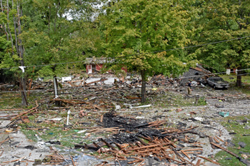 Scene of an exploded structure in rural area with burned building materials scattered