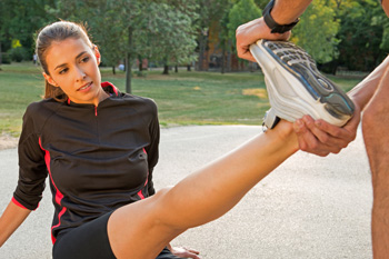 Jogger having leg stretched out at park by friend