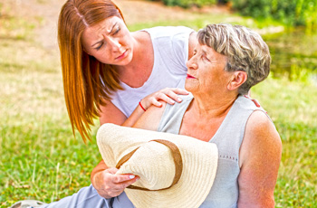 Older woman sitting on ground with other woman looking concerned in sunny area