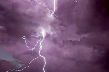 Lightning illuminates night sky with purple color