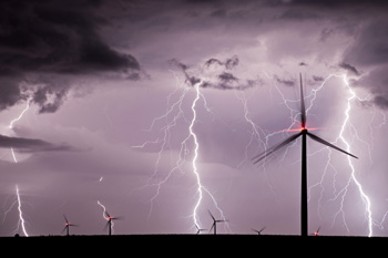 Multiple lightning bolts strike near windmill farm at night
