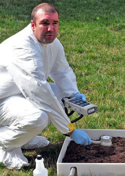 Man testing soil for contaminants like radioactive materials