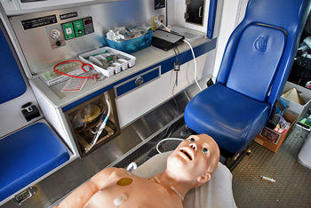 Human patient simulator on table inside ambulance