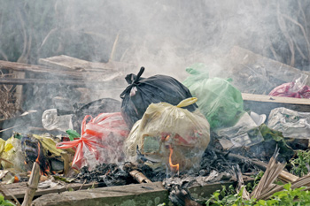 Pile of bags of trash burning