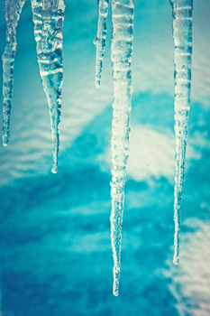 Five very pointy icicles in the foreground while a blue frozen surface sits just out of focus in the background