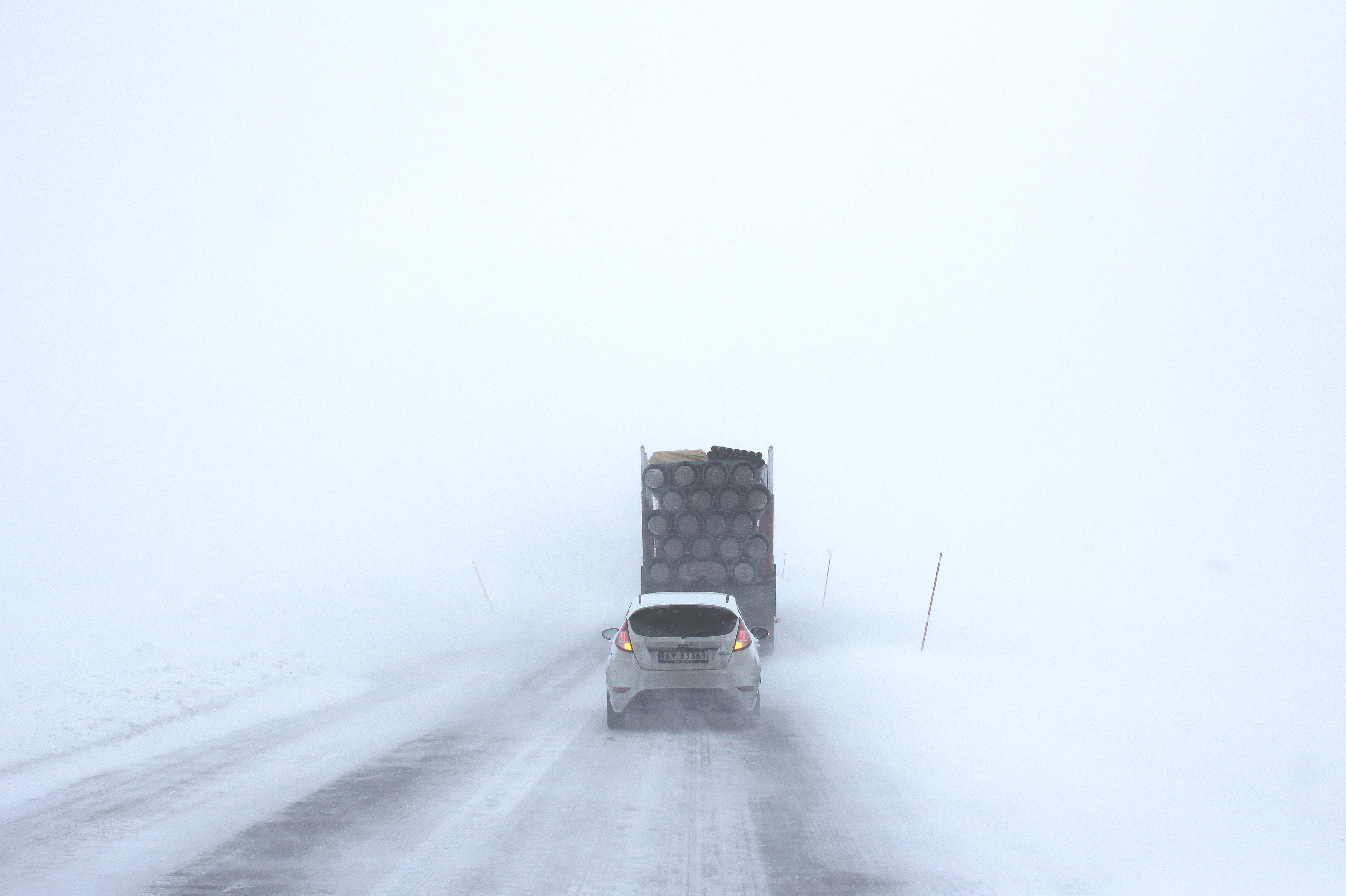 A foggy snowy drive with a car and a truck