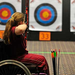 Women in wheelchair aiming at archery target