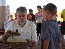 Dr. Rick Jones sharing information about archaeology with a young person.
