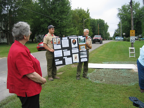 Members of Osgood Scout Troop 638, who presented the Colors for the dedication ceremony, are seen here holding an exhibit board for Diane Perrine Coon's presentation.