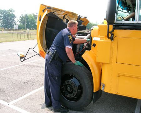 Master MCI Robert Burkhead inspects under the hood of a school bus.